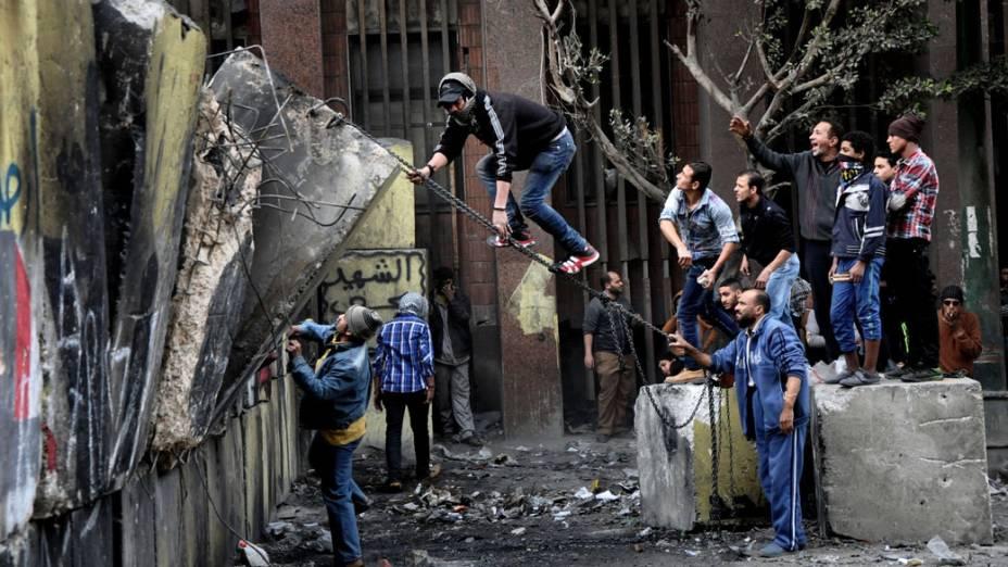 Manifestantes egípcios tentam derrubar um muro construído para impedi-los de chegar ao Parlamento e ao prédio do Gabinete perto da Praça Tahrir no Cairo, Egito