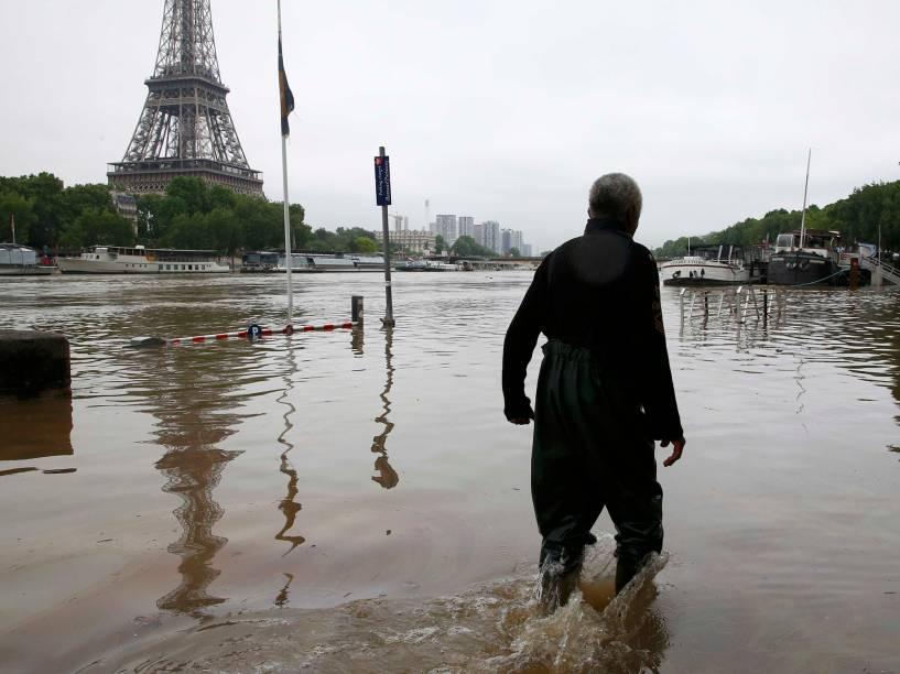 Homem caminha em uma avenida inundada às margens do Rio Sena, em Paris