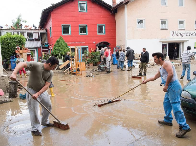 Moradores da cidade de Triftern ajudam a limpar a lama das ruas causada pelas fortes chuvas que atingiram a região, na Alemanha