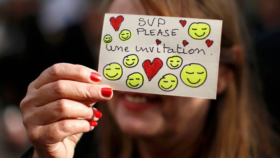 Uma fã é fotografada segurando um mini cartaz onde pede um bilhete de entrada para a cerimônia de abertura do 67º Festival de Cinema de Cannes