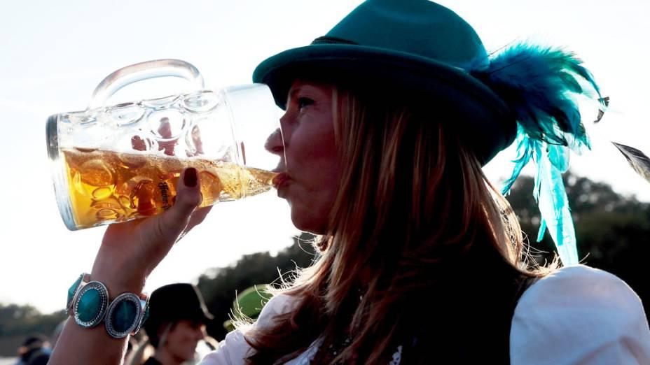 Mulher bebe cerveja fora de uma barraca durante o 180° Oktoberfest em Munique, na Alemanha