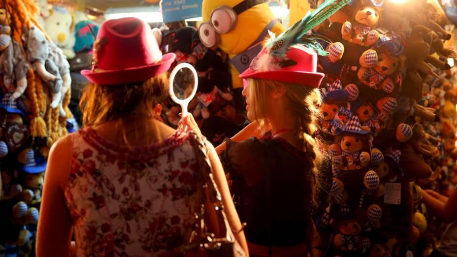 Mulheres experimentam chapéus em um quiosque durante o 180° Oktoberfest em Munique, na Alemanha