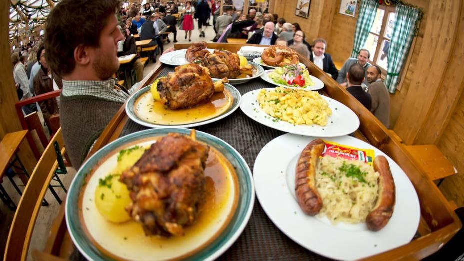 Um garçom traz uma bandeja grande de refeições no 180° Oktoberfest em Munique, na Alemanha