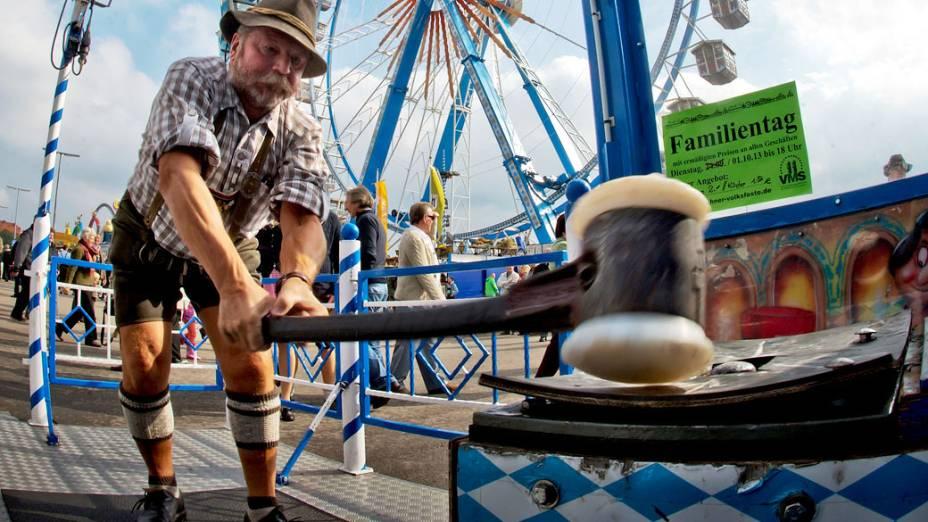 Visitante vestido de um bávaro em um tradicional Lederhosen participa de uma atração parque de diversões chamado Hau den Lukasno 180° Oktoberfest em Munique, na Alemanha