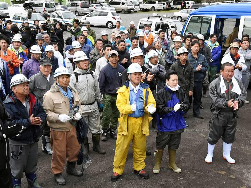 Membros da equipe de busca comemoram, após menino de 7 anos que estava desaparecido desde 28 de maio, ser encontrado vivo, no Japão