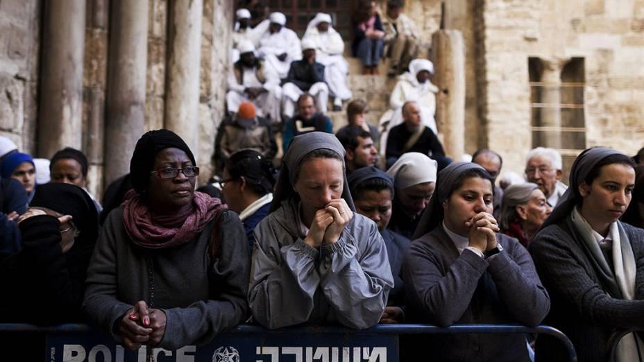 Fiéis oram enquanto aguardam abertura da Igreja do Santo Sepulcro, na cidade velha de Jerusalém, em Israel, na celebração da Sexta-feira Santa