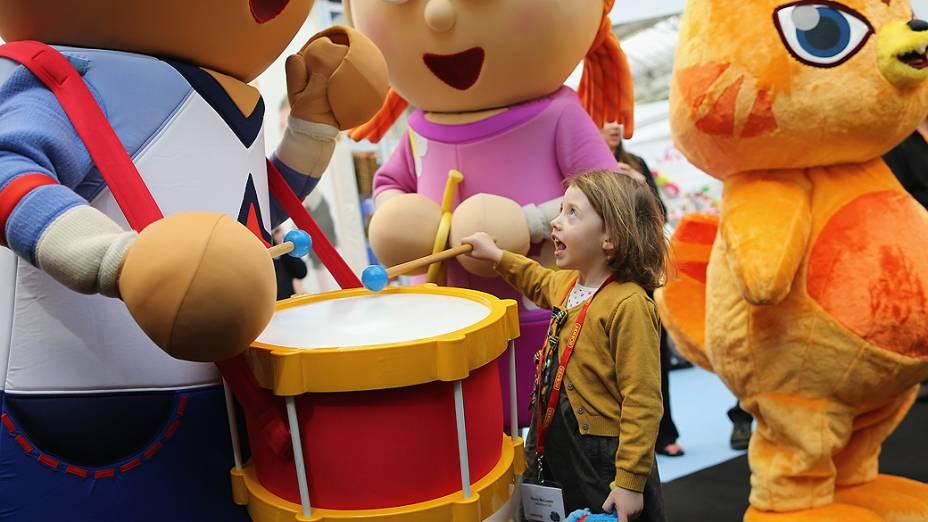 Garota de 4 anos interage com mascotes de desenho animado durante a feira anual de brinquedos de Londres