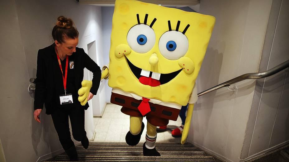 Homem vestido de Bob Esponja recebe ajuda para subir escadas durante a feira anual de brinquedos de Londres