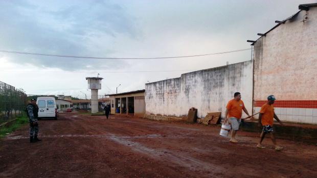 Detentos que trabalham na limpeza do Presídio São Luís I caminham sob olhar de PM do Batalhão de Choque