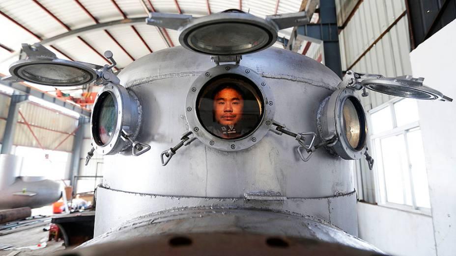Zhang Wuyi, senta em seu novo submarino, construído em Wuhan, na China. Zhang é um inventor amador e já fez sete miniaturas de submarinos. Um deles chegou a ser vendido a um empresário local por cerca de R$ 30 mil