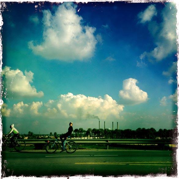 Foto tirada com um IPhone, mostra homem andando de bicicleta, na capital iraquiana Bagdá