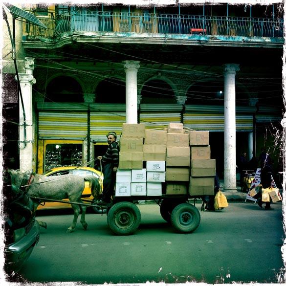 Iraquiano anda em uma carroça carregada de caixas, em Bagdá