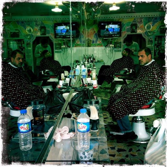 Foto tirada com um iPhone, mostra Iraquianos em uma barbearia, em Bagdá