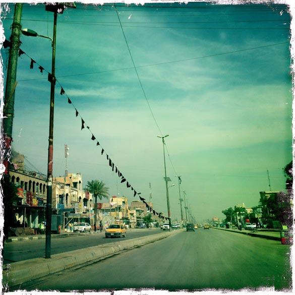 Carros em uma rua de um bairro pobre da capital iraquiana Bagdá