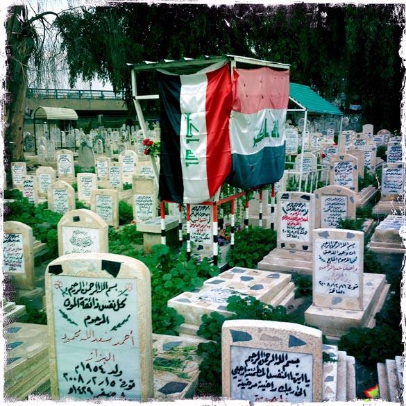 Bandeiras iraquianas sobre lápides no cemitério dos mártires sunitas em Bagdá