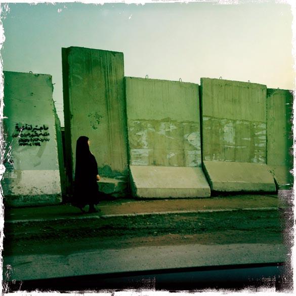Mulher iraquiana anda em frente à barreiras de concreto, em Bagdá