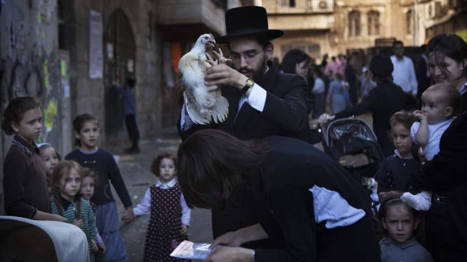 """Em Jerusalém, judeu ultra-ortodoxo realiza o ritual Kaparot, no qual """"transfere"""" os pecados para uma galinha"""