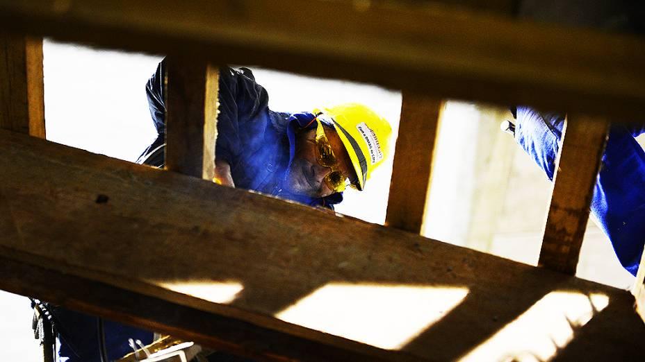 Carpinteiro prende placa de madeira durante o expediente, na construção do estádio do Itaquerão