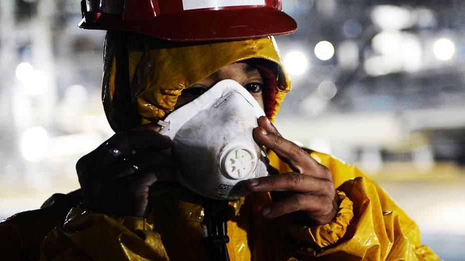 Operário trabalha com uniforme composto por mangas compridas, luvas, botas, capacete e equipamentos de segurança