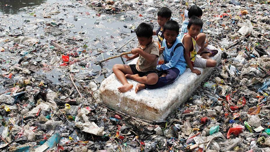 Crianças improvisam bote para flutuar em um rio tomado pelo lixo em Jacarta, na Indonésia