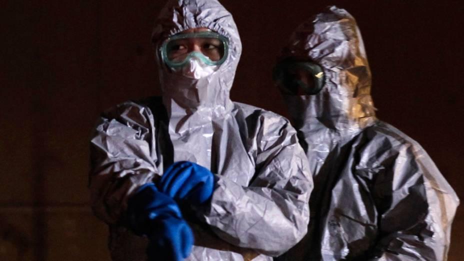Oficiais japoneses usam roupas especias para evacuar moradores da cidade de Fukushima - 13/03/2011