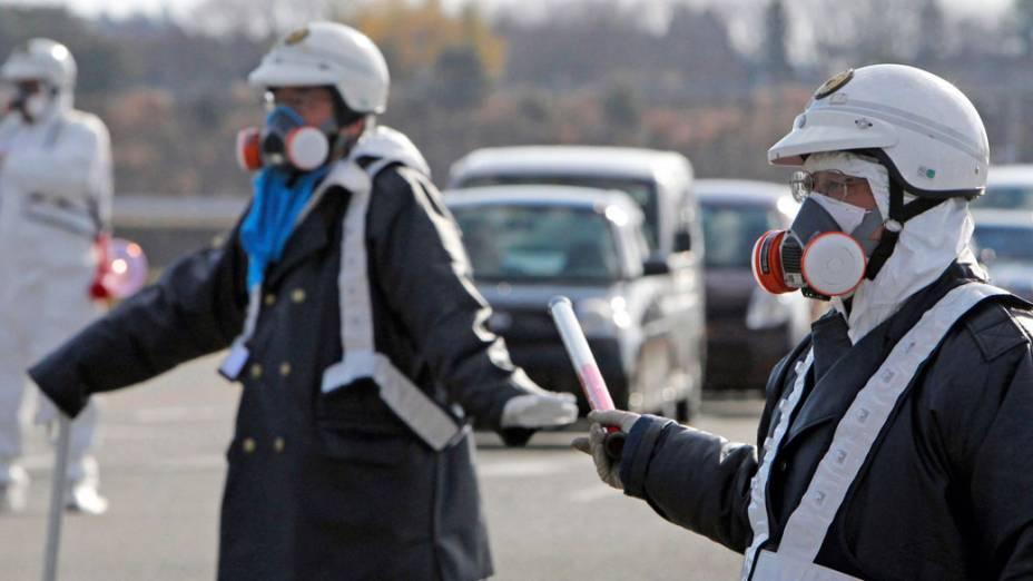 Oficiais japoneses usam proteção especial para evacuar moradores da cidade de Fukushima - 12/03/2011