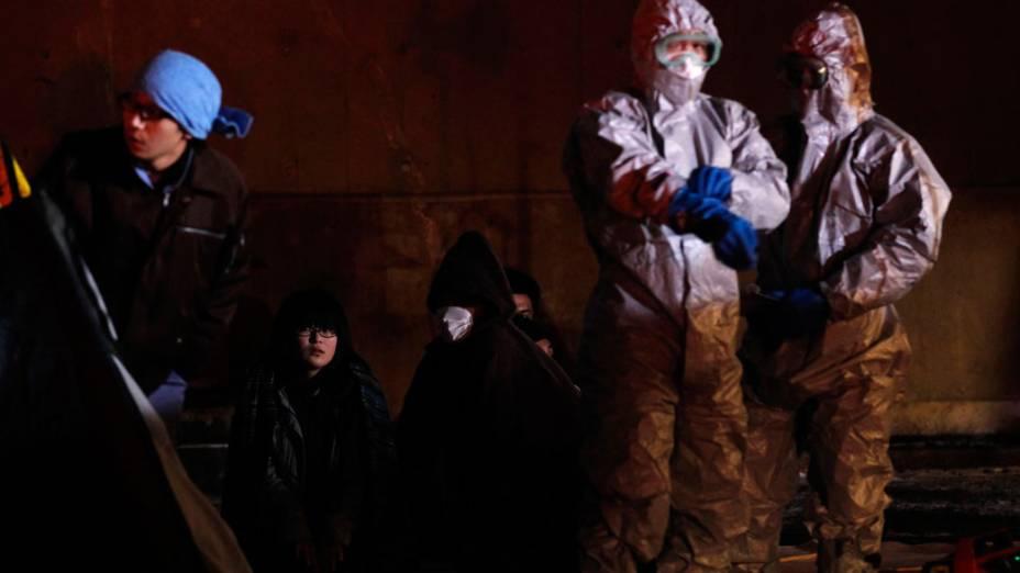Oficiais próximos a famílias que evacuaram a área perto da usina nuclear de Fukushima, no Japão