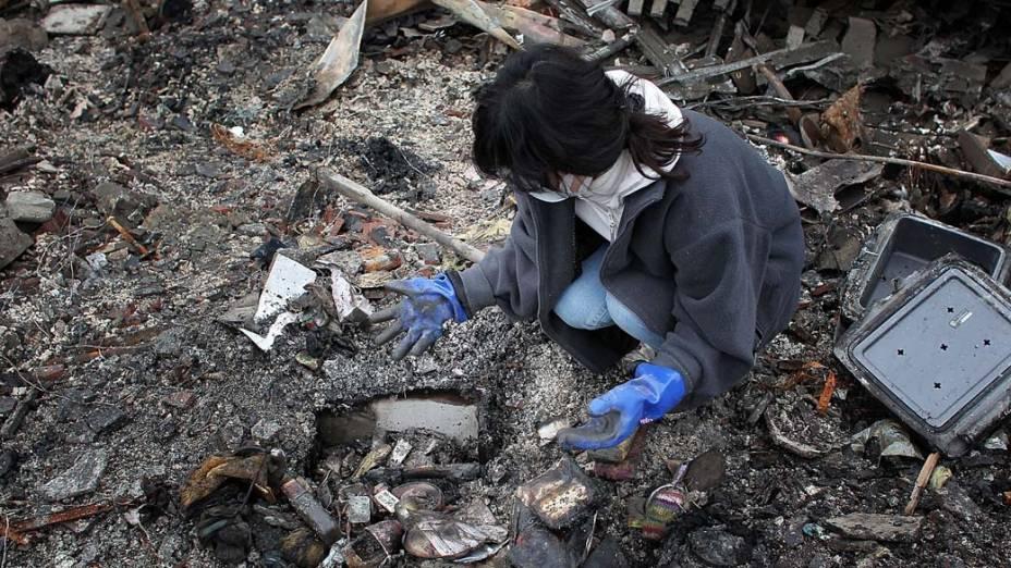 Akiko Hatareyama procura objetos e lembranças no local onde estava a sua casa em Kesennuma, Japão