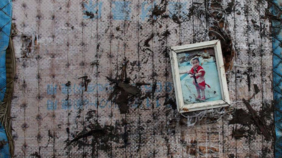 Foto de criança em escombros de casa na cidade de Kensennuma, Japão