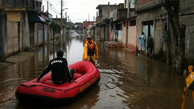Botes da Defesa Civil estão sendo utilizados para fazer o transporte das pessoas, mas alguns ainda se arriscam e andam nas águas contaminadas - 26/01/2012