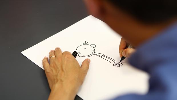 O criador de Diário de um Banana, Jeff Kinney, desenha o personagem Greg Heffley em visita ao Brasil