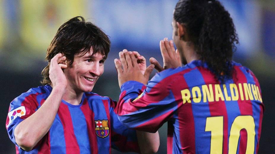 Lionel Messi e Ronaldinho, jogadores do Barcelona, comemoram depois de vencer o Villarreal durante partida do campeonato espanhol, em 2005