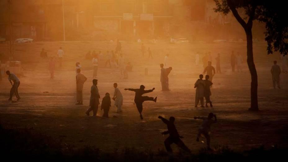 Paquistaneses jogam críquete em parque na cidade de Islamabad