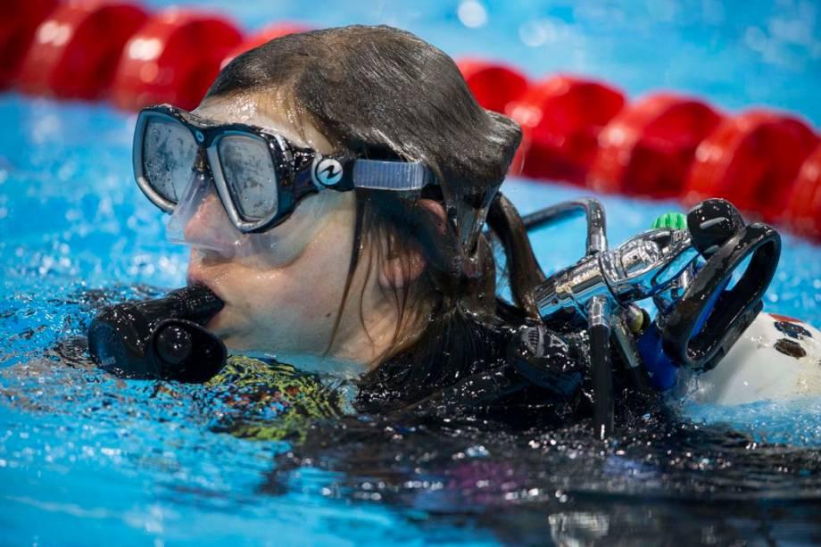 Mergulhadora que instala câmera sob a água na piscina olímpica