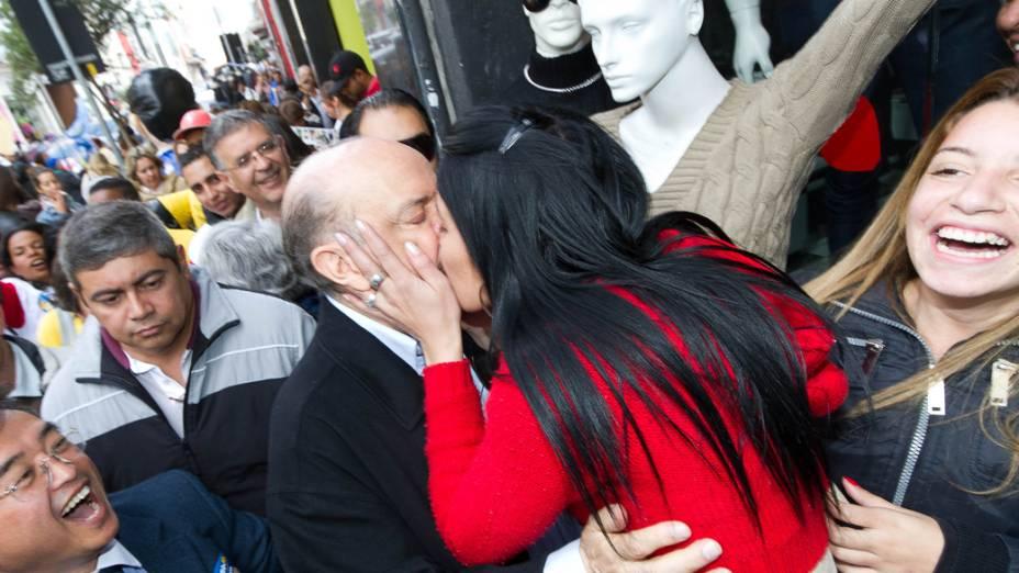 O candidato à Prefeitura de SP José Serra é beijado por mulher durante caminha no bairro do Bom Retiro, centro, nesta quinta-feira