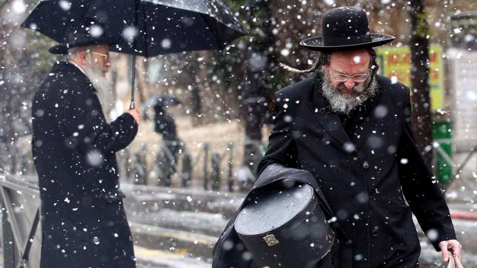 Judeus ultra-ortodoxos caminham sob a neve em Jerusalém, Israel