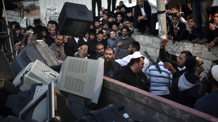 Judeus ultra ortodoxos jogam televisões durante protesto contra a indecência na TV israelense, em Jerusalém