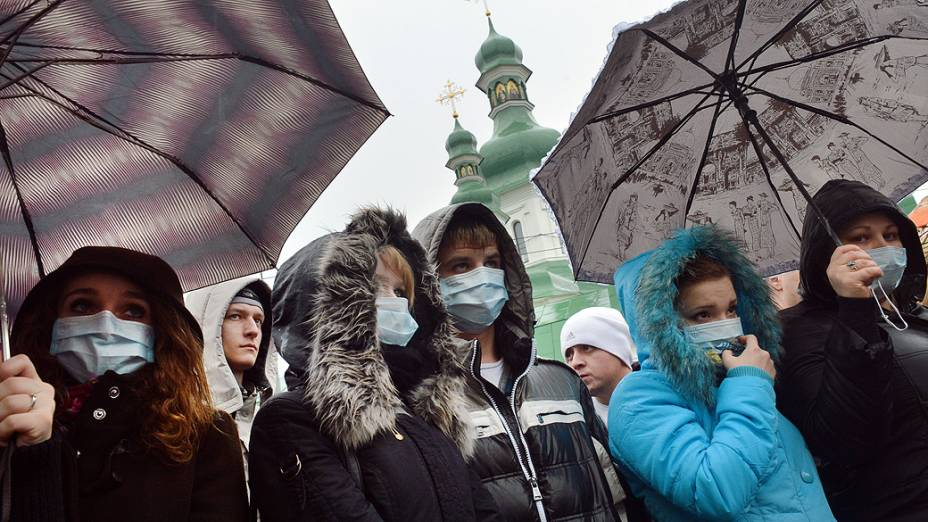 Ucranianos usam máscaras durante um protesto na capital Kiev, nesta terça-feira (13), onde exigem um aumento do financiamento de tratamento de doenças, como Aids e hepatite