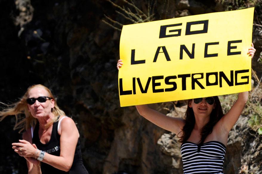 """Fã espera Lance Armstrong com a placa """"Go Lance Livestrong"""", uma referência a fundação do ciclista"""