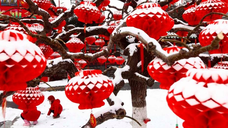Criança brinca entre lanternas cobertas de neve em Pequim.