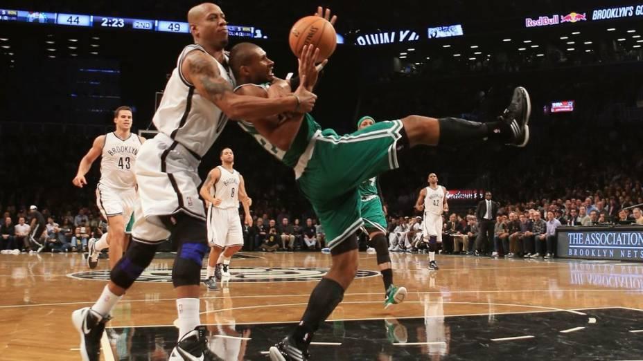 Leandrinho (à dir.) sofre falta no jogo entre Boston Celtics e Brooklyn Nets
