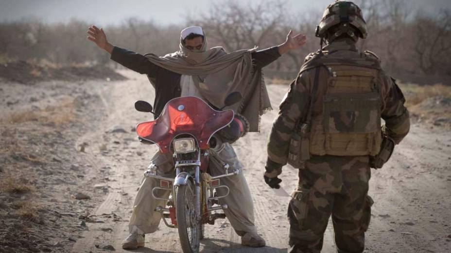 Legionário francês inspeciona motociclista afegão na província de Kapisa, Afeganistão