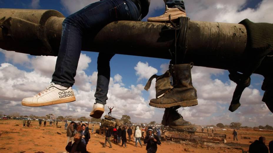 Rebeldes comemoram após ataque aéreo, que destruiu tanques das forças de Muamar Kadafi, próximo a Bengasi