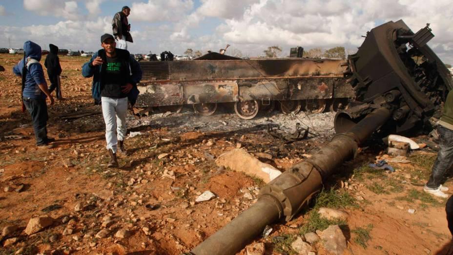 Rebeldes observam destroços de tanque atingido por ataque aéreo