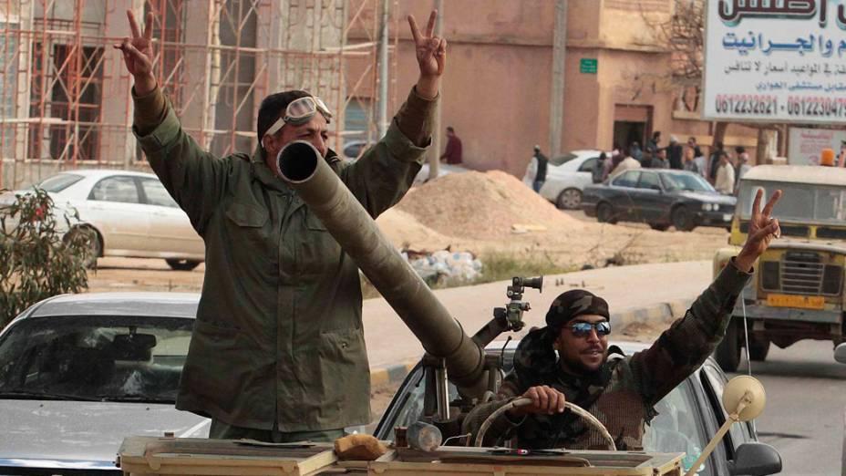 Rebeldes comemoram após ataque aéreo, que destruiu tanques das forças de Muamar Kadafi, em Bengasi