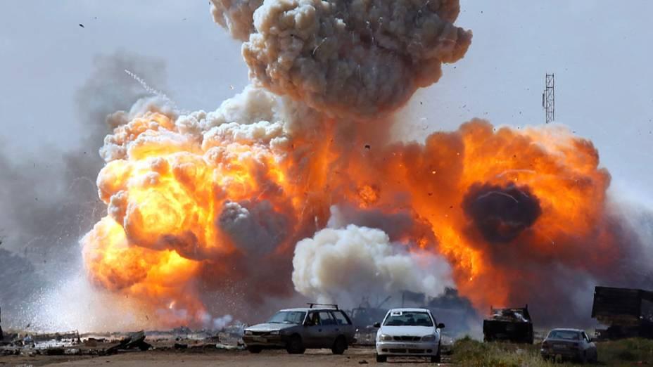 Veículos das forças leais do líder Muamar Kadafi explodem após ataque aéreo em estrada que liga Bengasi e Ajdabitah, na Líbia