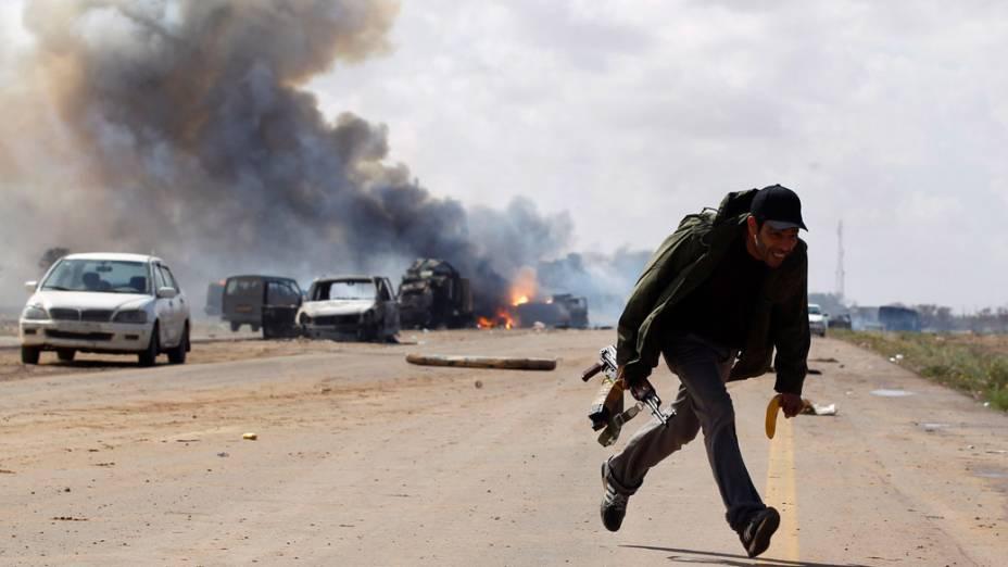 Rebelde líbio corre durante ataque aéreo contra forças de Muamar Kadafi, em estrada que liga Bengasi e Ajdabitah, na Líbia