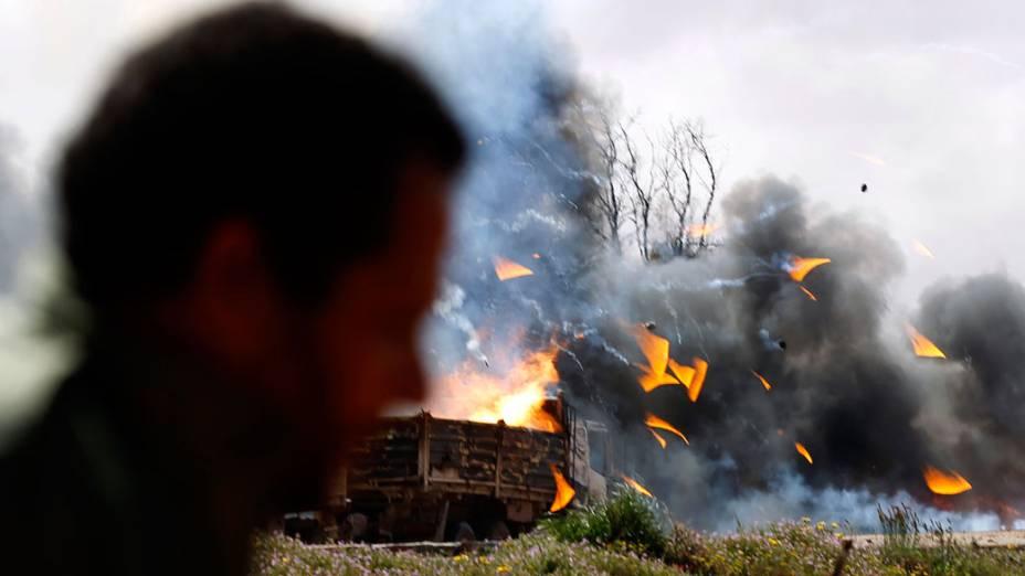 Rebeldes observam destroços de caminhões atingidos por ataque aéreo