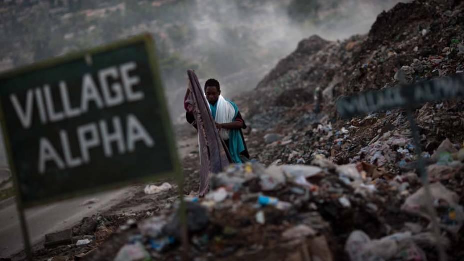 Em Porto Príncipe, homem recolhe roupas no lixão