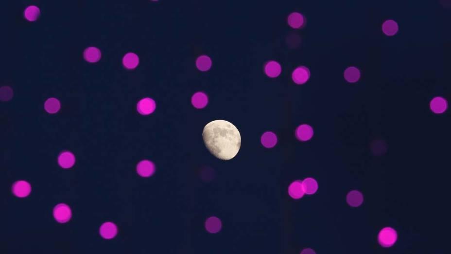 A lua vista através de vidro com luzes refletidas em parque em Hong Kong, China